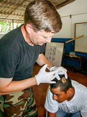 Dr. Steve Ritter treating a scalp wound.