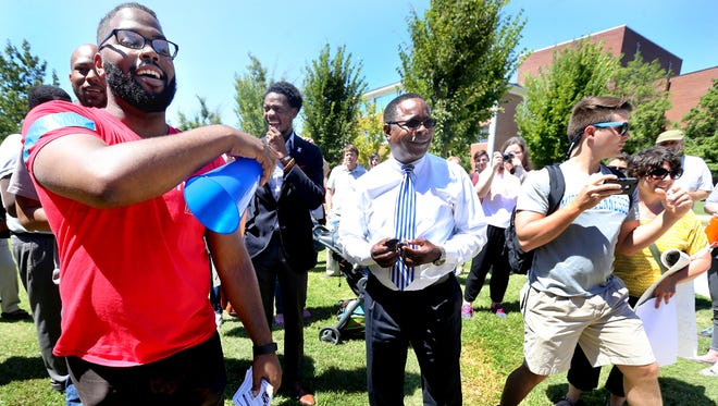 Forrest protest leader Joshua Crutchfield, left introduces MTSU President Sidney McPhee, center, to speak on the name of the Forrest building at the end of a march and rally, on Thursday, August 27, 2015, to protest the name of the ROTC building.