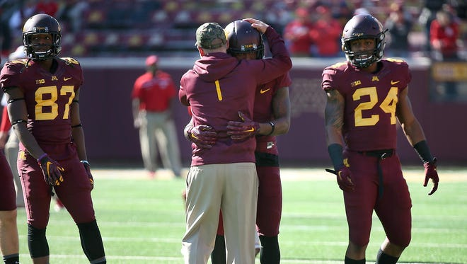 Coach Jerry Kill hugs Minnesota wide receiver KJ Maye before a Oct. 17 game against Nebraska at TCF Bank Stadium in Minneapolis. Kill abruptly retired because of health reasons on Wednesday, ending his efforts to rebuild the Golden Gopher football program during a tenure that included a series of game-day seizures.
