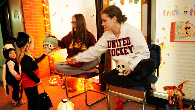 During the annual Halloween in the Halls event in October 2014, College of St. Benedict students Alex Rudelius, left, and and Sam Strout had out candy to young trick-or-treaters in Aurora Hall