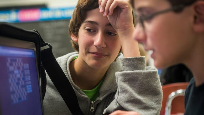 Hanover Middle School students Nathanyal Mummert, left, and Michael Corbin, right, collaborate on a game exercise called Hnefatafil on Nov. 23, 2015.