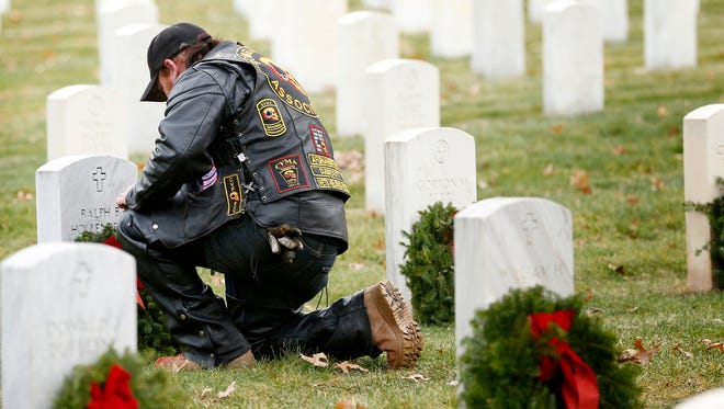 A veteran pauses momentarily to pay his respect to a deceased service member at Woodlawn National Cemetery in Elmira Saturday during the Wreaths Across America campaign.