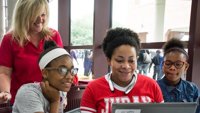 Kim Prejean assists Amy Battles and her daughters Emya Black and Elisia Black to register at the Fall Frenzy at the Cajundome in November. The event showcases all Schools of Choice academies.