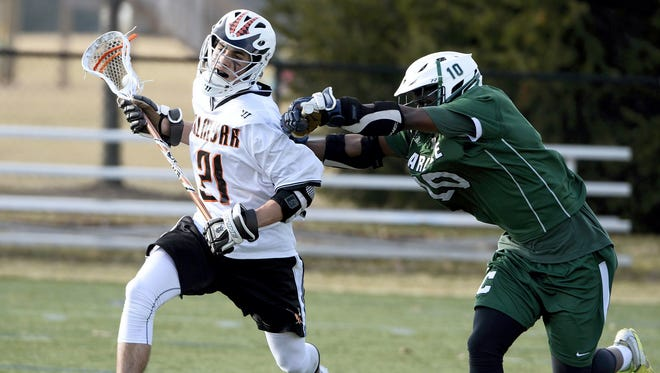 Palmyra junior Peter Robertson takes a hit from Carlisle's Justin Moore during a regular-season game last year. Robertston scored three goals against the Thundering Herd on Thursday.
