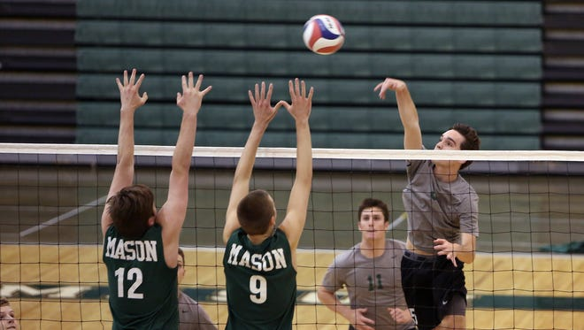 McNicholas' Matt Barbera blasts a shot past Mason's Austin Brown, 9, and Jacob Grove.