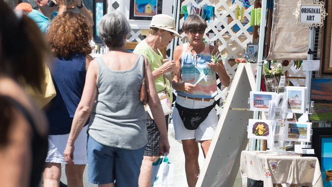 Visitors explore the artist's booths at the St. Peter's Episcopal Church 50th Anniversary Art Show in Lewes.