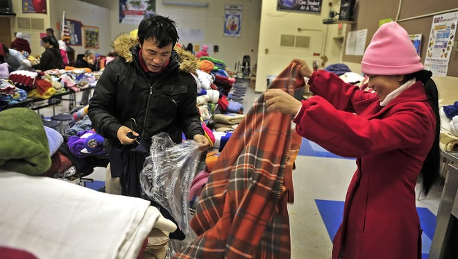 Neingkhui Shing, left, and his wife Manertee take a look at a blanket at Haywood Elementary School in 2014.