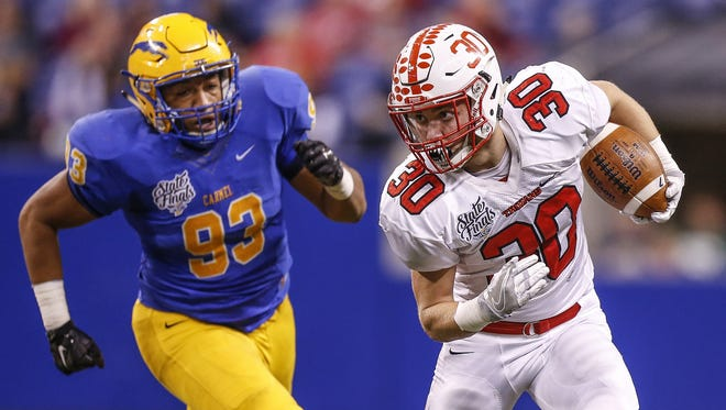 Center Grove Trojans' Titus McCoy (30) makes his way upfield against Carmel in the Class 6A state title game at Lucas Oil Stadium on Friday, Nov. 25, 2016.