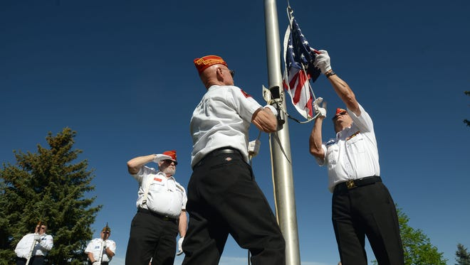 Ken Dimick, left, and Dennis Anderson, right, raise the American Flag, at the Veterans Memorial service at the Veterans Memorial in Edora Park Monday morning May 27, 2013.