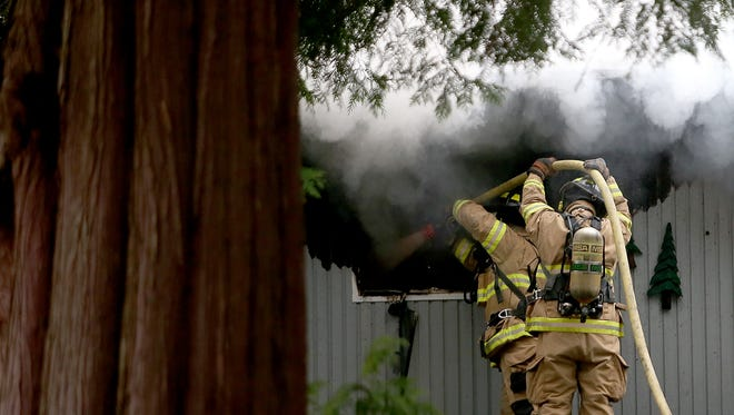 Bremerton Firefighters man a hose at the scene of a residential structure fire on Pinecone Drive in Bremerton on Friday, Dec. 30, 2016.