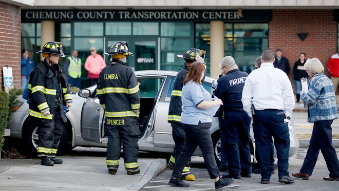 A car sits pressed against the a bush at the post office building in Elmira early Wednesday afternoon.