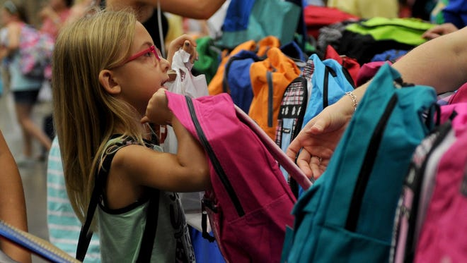 Shaleigh Sullivan picks out a backpack filled with school supplies at Project Back to School Roundup Saturday, Aug. 12, 2017 in the Ray Clymer Exhibit Hall at the MPEC.