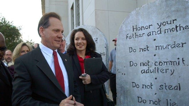 This Nov. 12, 2003 file photo shows Roy Moore looking at a Ten Commandments display as he arrives at the Judicial Building in Montgomery, Ala.