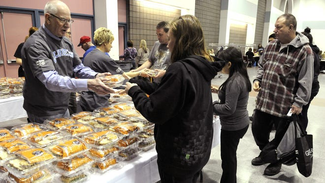 Volunteer DeWayne Mareck gives out sandwiches in March 2015 during Project Homeless Connect at the River's Edge Convention Center.