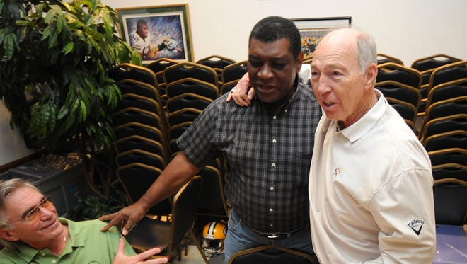 Green Bay Packers Hall of Fame archivist Tom Murphy, left, and fromer quarterback Bart Starr, right, greet Dave Robinson as he arrives at Stadium View  for a Lombardi's Titletown Champions alumni charity event on Sept. 20, 2008.