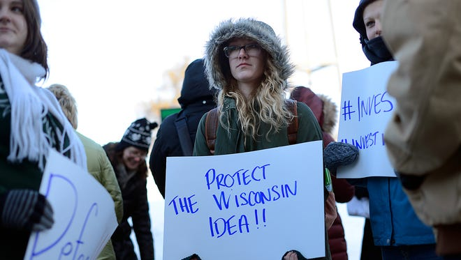 In middle, Megan Ryan, a senior at UW-Green Bay, holds a sign as she participates in the University of Wisconsin Students Against Education Cuts rally outside the University Union at UW-Green Bay.