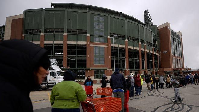 People gather outside Lambeau Field to receive food Wednesday at the Brown County Food Drop.