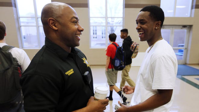 School resource officer Irvin Turner chats with senior Larry Wilson before class at Siegel High School in 2015.