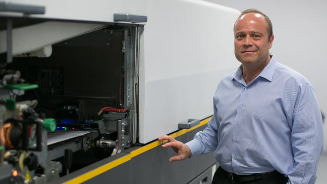 Phoenix Graphics President Sal DeBiase, III, with the Kodak NexPress at his company's headquarters in Rochester on Thursday, April 9, 2015.