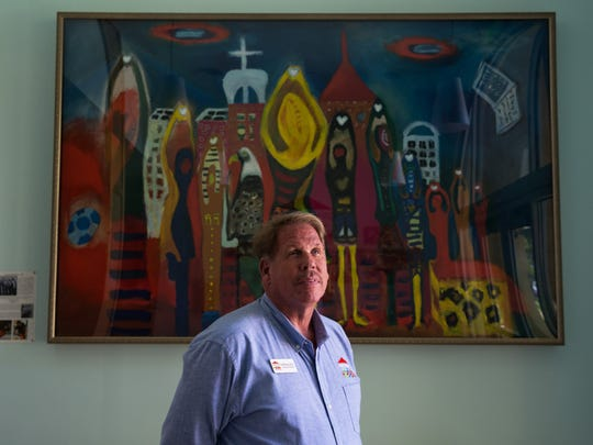 Grace Place for Children and Families Executive Director Tim Ferguson stands in front of a painting inspired by the children of the organization in Naples on Friday, Oct. 14, 2016.