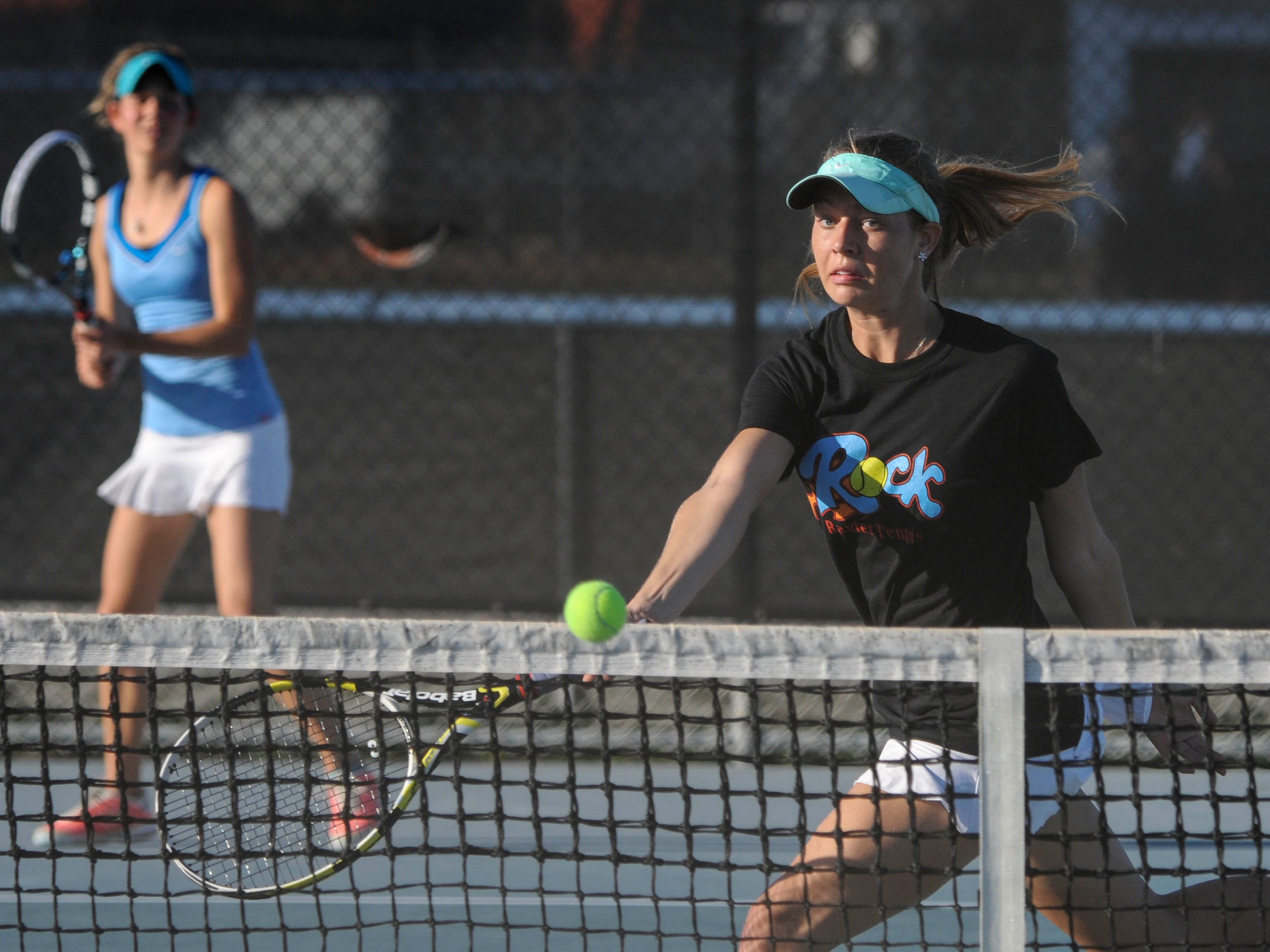 Emily Sidor watches as her sister Katie sends a drop shot over the net during a doubles match this season.