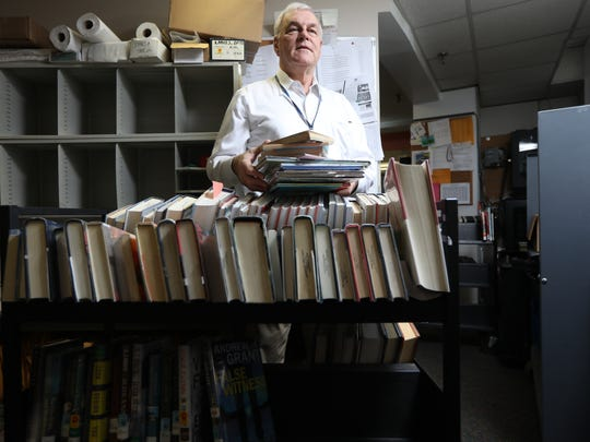 Teaneck Library Director Michael McCue, on Tuesday, Jan. 30, with about 200 backlogged items that need to be delivered to other libraries in North Jersey. The library just caught up on delivering items on Monday and had collected this next batch in less than 24 hours.