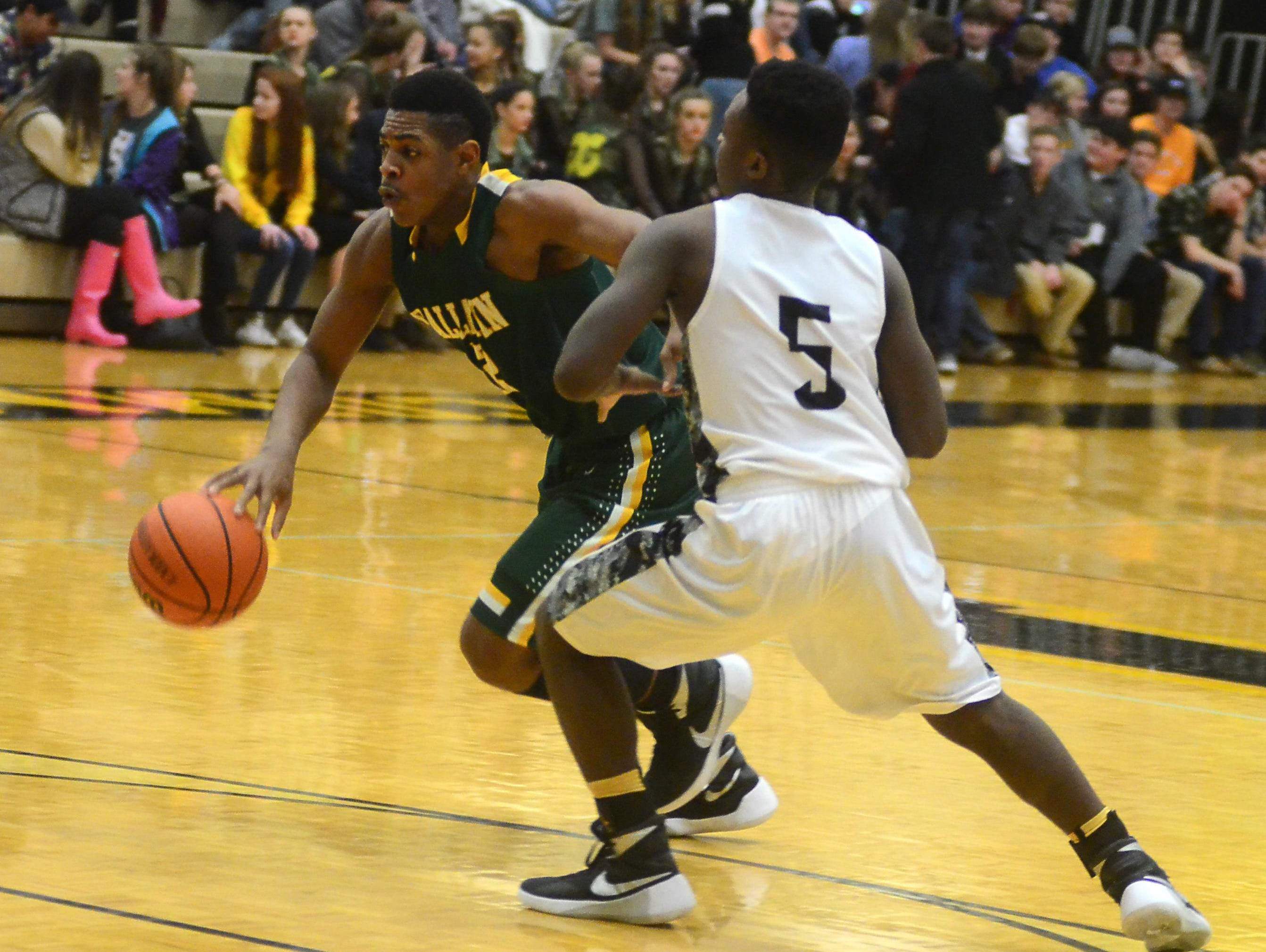 Gallatin High sophomore guard Zyun Mason dribbles into the lane as Hendersonville sophomore Dyilin Hoosier defends during third-quarter action. Mason scored 15 points in the Green Wave's double-overtime win.