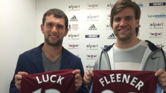 Andrew Luck and Coby Fleener are shown holding soccer jerseys.