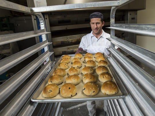 Pastry chef Jeremy Gullen pulls freshly-baked hot cross