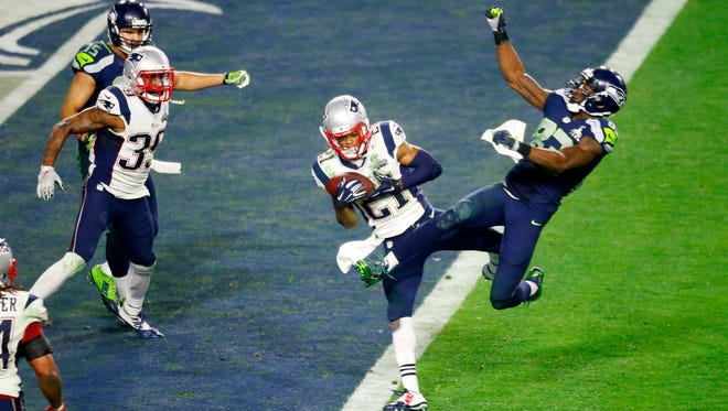 Patriots corner back Malcolm Butler intercepts a pass intended for Seahawks wide receiver Ricardo Lockette in the closing minute of Super Bowl XLIX at University of Phoenix Stadium in Glendale on Feb. 1, 2015. The Patriots Brandon Browner and the Seahawks Jermaine Kearse look on. The Patriots won the game 28-24.