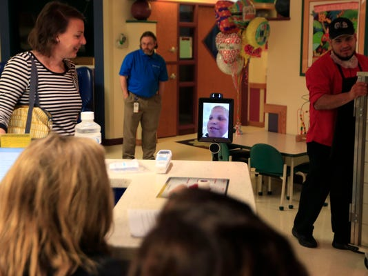 Ian Horner tells a joke at a nurses' station via a robot named REX in the hallways at Children's Mercy Hospital in Kansas City, Mo., Tuesday, May 16, 2017. The robot is a four-foot tall post with an iPad and camera on top, anchored by wheels similar to a Segway's. (AP Photo/Orlin Wagner)