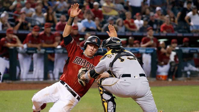 Arizona Diamondbacks' Jake Lamb, left, is tagged out as he tries to score by Pittsburgh Pirates' Chris Stewart, right, during the 10th inning of a baseball game, Sunday, April 24, 2016, in Phoenix.