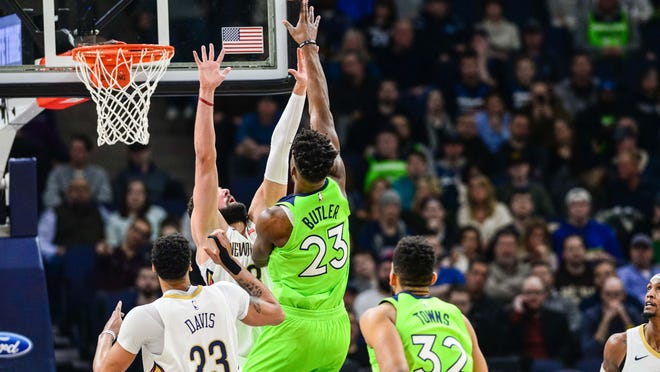 Feb 3, 2018; Minneapolis, MN, USA; Minnesota Timberwolves guard Jimmy Butler (23) shoots the ball as New Orleans Pelicans forward Anthony Davis (23) and forward Nikola Mirotic (3) defend during the second quarter at Target Center. Mandatory Credit: Jeffrey Becker-USA TODAY Sports