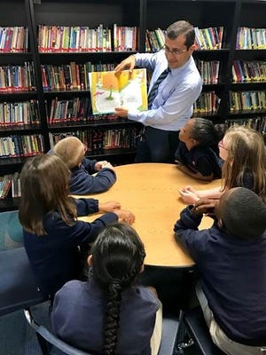 Tallahassee School of Math and Science principal Ahmet Temel reads to students