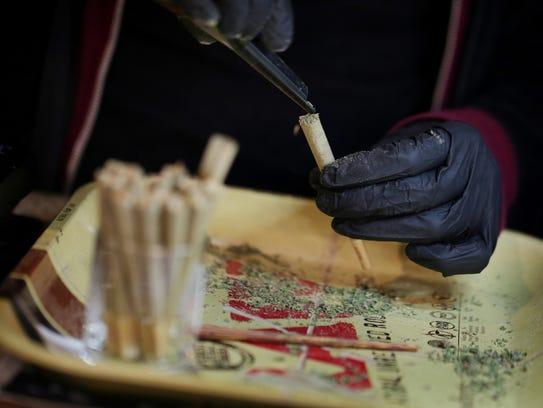 A budtender pre rolls marijuana cigarettes for sale