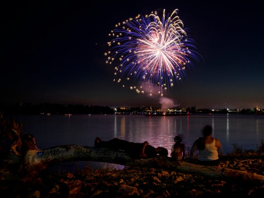 "Chris Peach, left to right, Kylan Peach, 6, and Amber Coomes relax on a large decorated driftwood tree that they nicknamed ""Peach's Peace Tree"" while watching the ""Fireworks on the Ohio"" celebration in Downtown Evansville, Indiana, July 4, 2018. Chris recently painted sayings onto the washed up tree that he found along the Ohio riverbank such as ""love yourself"" and ""smile, happy looks good on you."" The group decided it would be a good place to view the Independence Day fireworks from."