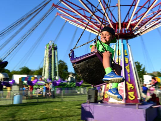 Johnston kindergartner Rylan Ravens smiles at his mom as he rides the swing ride at the Green Days carnival in 2016.