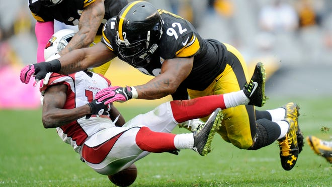 Arizona Cardinals wide receiver John Brown (12) fumbles after being hit by Pittsburgh Steelers outside linebacker James Harrison (92) in the third quarter of an NFL football game on Sunday, Oct. 18, 2015, in Pittsburgh.