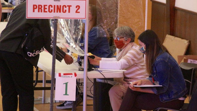 Poll workers assist a voter Tuesday, Nov. 3, at Holland Heights Christian Reformed Church in Holland.