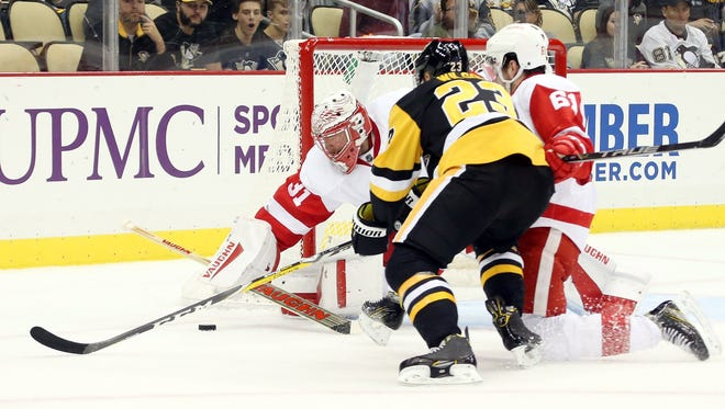 Detroit Red Wings goalie Jared Coreau (31) makes a save against Pittsburgh Penguins left wing Scott Wilson (23) as defenseman Xavier Ouellet (61) defends during the second period at the PPG Paints Arena.