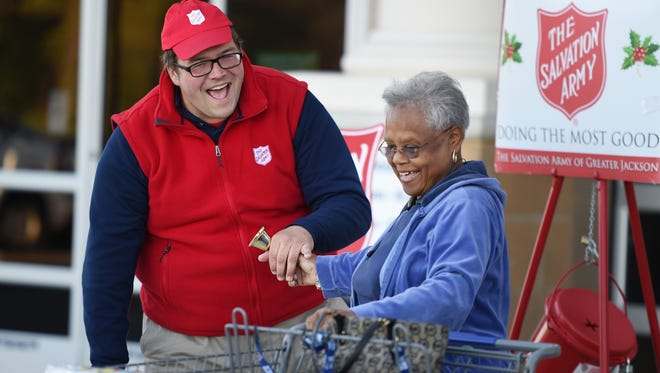 Salvation Army bell ringer Samuel Harrison shares a laugh with Sam's Club customer Bertha Swan of Vaughan after letting her ring the bell at his kettle outside the Madison store Thursday afternoon.