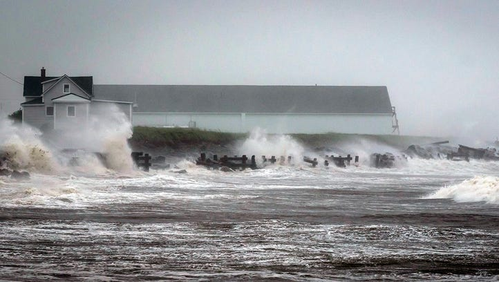 Waves crash against rock embankments that protect the Escuminac road against erosion during Tropical Storm Arthur in Escuminac, New Brunswick, on July 5.  Arthur hit Canada's Maritime provinces with near-hurricane strength winds and torrential rains, knocking out power to nearly 200,000 customers.