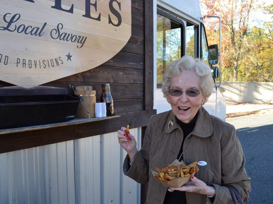Olive McCready, a resident of Mallard Landing, tries the Trump Fries at the Vittles food truck parked utside the Ward Museum on Election Day.