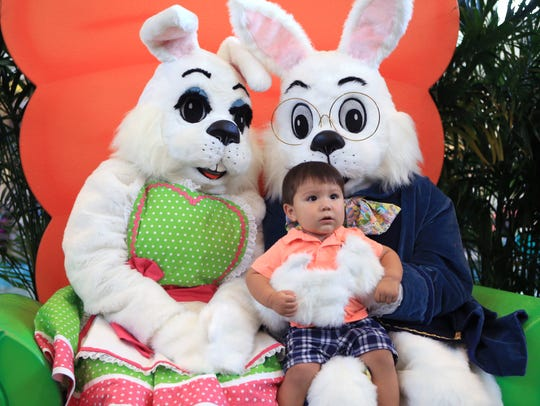 Enrique Jaime, 1, takes a photo with the Easter bunnies