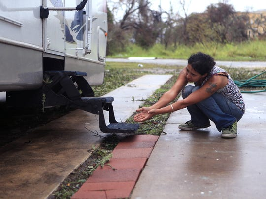Jessica Jackson tries to coax a dog that was left behind during Hurricane Harvey in Fulton, TX from underneath a trailer near Bronte Street on Monday, August 28, 2017. Officials said animals left behind during the hurricane have been a major problem because the county doesn't have the resources to handle them and cannot address the problem.