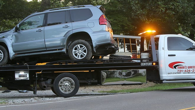 A wrecked vehicle is carried away on a truck along Christmasville Road in Jackson, Tenn., on Wednesday, Aug. 24, 2016.