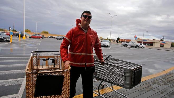 Taylor Kempton retrieves shopping carts on Nov. 3 at the Safeway on West Main Street in Farmington.