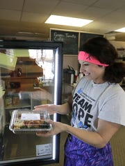 Jacole Hall, owner of Mission Meal Prep, places a prepared dinner into a cooler at Green Tomato in Appleton.