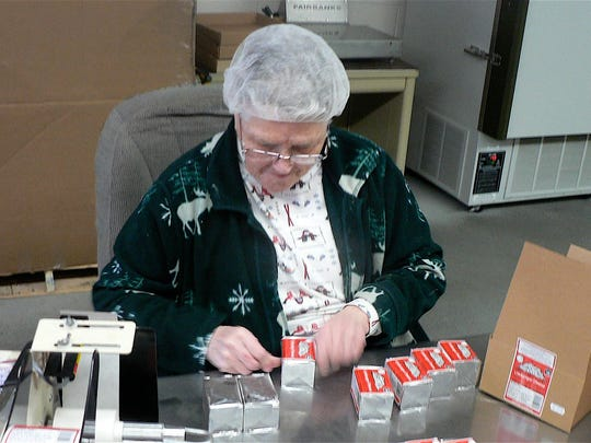 Carol Tourdot  applies labels to Limburger cheese. She has worked at Chalet Cheese Co-op for over 40 years.