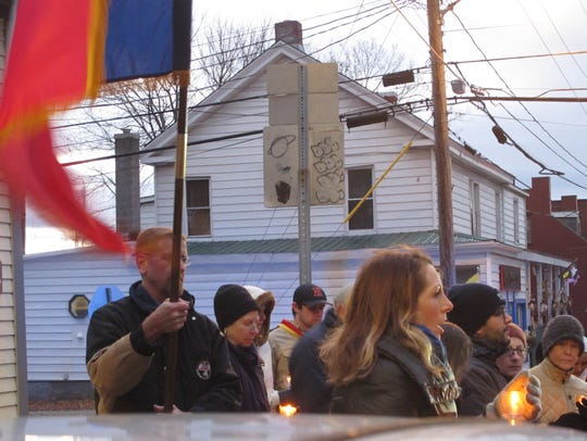 People gather for a candlelight vigil Saturday evening
